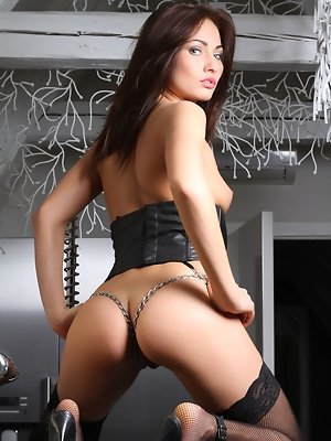 The goddess Michael Isizzu portrays a sultry vixen in black leather bustier with metal chains, fishnet stockings and leather stilettos.